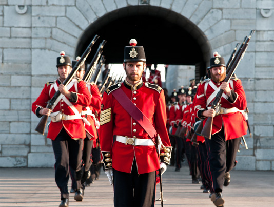 Armed historical uniformed officers in formation at Kingston Fort Henry